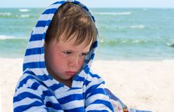 Little cute kid hurt and pouted, disappointed. Beautiful little kid with atopic dermatitis on the background of the sea, royalty free stock images