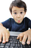 A little cute kid with a laptop isolated, surprise