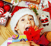 Little cute kid in santas red hat with handmade gifts, toys vint Royalty Free Stock Images