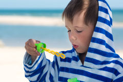 A little cute kid in a striped robe blows soap bubbles against the background of the sea and washed spit, Stock Images