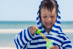 A little cute kid in a striped robe indulges, lets bubbles on the background of the sea Royalty Free Stock Photo