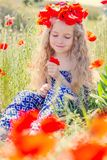 Little cute little girl in a wreath of poppies Stock Photo
