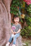Little cute lovely girl Chinese child smile laugh play by a tree hold lollipop at summer park nature happiness childhood. Asian Chinese little cut lovely girl stock photo