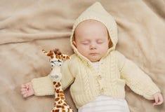 Little cute newborn baby boy sleeping with giraffe. Sleeping cute newborn baby, maternity concept, soft image of beautiful family stock photo
