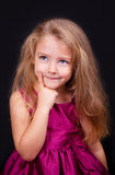 Little cute pensive girl in a bright pink dress Stock Images