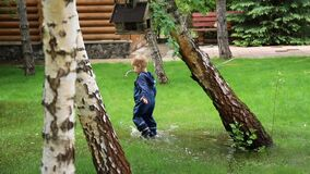 Little cute playful caucasian blond toddler boy enjoy have fun playing jumping in dirty puddle wearing blue waterproof