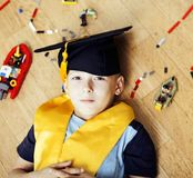 Little cute preschooler boy among toys at home in graduate hat s Stock Image