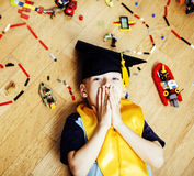 Little cute preschooler boy among toys lego at home education in graduate hat smiling posing emotional, lifestyle people. Concept close up stock photos