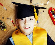 Little cute preschooler boy among toys lego at home education in graduate hat smiling posing emotional, lifestyle people. Concept close up stock image
