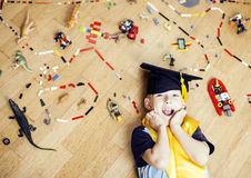 Little cute preschooler boy among toys lego at home education in graduate hat smiling posing emotional, lifestyle people. Concept close up royalty free stock photography