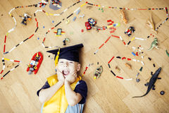 Little cute preschooler boy among toys lego at home in graduate hat smiling posing emotional, lifestyle people concept Royalty Free Stock Images