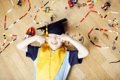 Little cute preschooler boy among toys lego at home in graduate hat smiling posing emotional, lifestyle people concept. Close up royalty free stock images