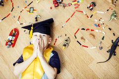 Little cute preschooler boy among toys lego at home in graduate hat smiling posing emotional, lifestyle people concept Royalty Free Stock Image