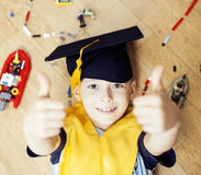 Little cute preschooler boy among toys lego at home in graduate hat smiling posing emotional, lifestyle people concept Royalty Free Stock Photos