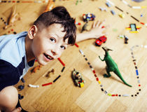 Little cute preschooler boy among toys lego at home happy smiling, lifestyle people concept. Close up stock photography
