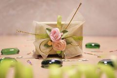 Little cute present with roses on the strip. Little cute present on the table surrounded by sparkle and green decorations royalty free stock photo