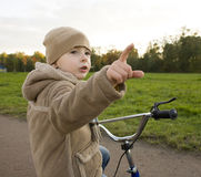 Little cute real boy on bicycle emotional smiling close up outside in green amusement park Stock Photo