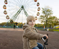 Little cute real boy on bicycle emotional smiling close up outside in green amusement park Stock Photos
