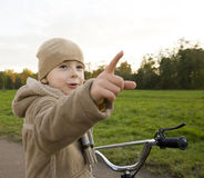Little cute real boy on bicycle emotional smiling close up outside in green amusement park Stock Photography