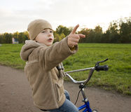 Little cute real boy on bicycle emotional smiling close up outside in green amusement park Stock Image