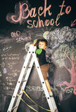 Little cute real boy at blackboard in classroom, back to school Royalty Free Stock Image