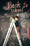Little cute real boy at blackboard in classroom, back to school close up Royalty Free Stock Photos