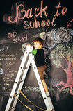 Little cute real boy at blackboard in classroom, back to school Stock Photo
