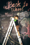 Little cute real boy at blackboard in classroom, back to school, Stock Photography