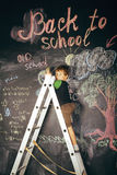 Little cute real boy at blackboard in classroom Royalty Free Stock Image