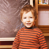 Little cute real boy at blackboard in classroom, back to school painting Royalty Free Stock Image