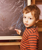 Little cute real boy at blackboard in classroom, back to school painting Royalty Free Stock Photo