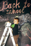 Little cute real boy at blackboard in classroom Stock Photography