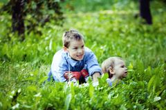 Little cute real boy among green tree, outdoor lifestyle people. Concept close up Royalty Free Stock Photos
