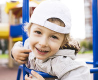 Little cute real boy playing on playground, hanging on gymnastic ring cheerful Royalty Free Stock Image