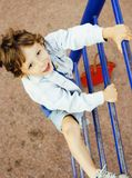 Little cute real boy playing on playground, hanging on gymnastic Royalty Free Stock Image