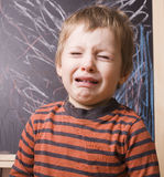 Little cute real boy screaming and crying at school near blackboard close up Royalty Free Stock Images