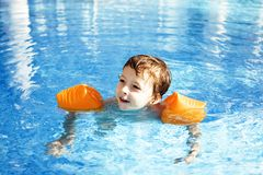 Little cute real boy in swimming pool close up smiling, lifestyl Royalty Free Stock Image