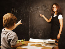 Little cute real boy with teacher in classroom at Stock Photography