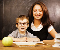 Little cute real boy with teacher in classroom at Stock Image