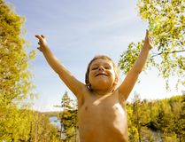 Little cute real boy among tree hight, outdoor lifestyle people. Concept close up Stock Photography