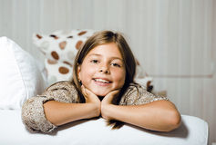 Little cute real girl at home interior smiling. Adorable stock image