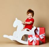 Little smiling baby sitting on a white horse, wooden rocking royalty free stock photo