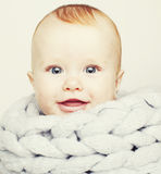 Little cute red head baby in scarf all over him close up isolate Royalty Free Stock Photography