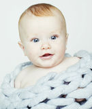 Little cute red head baby in scarf all over him close up isolate Stock Images