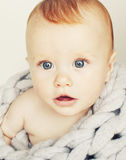 Little cute red head baby in scarf all over him close up isolate Royalty Free Stock Images