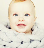Little cute red head baby in scarf all over him close up isolate Royalty Free Stock Photos