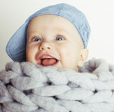 Little cute red head baby in scarf all over him close up isolated, adorable kid, hipster child close up smiling happy Royalty Free Stock Images