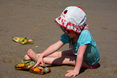 Little cute redhead child plays with sand on Bali beach Stock Image