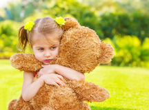Sad girl with teddy bear. Little cute sad girl holding in hands brown teddy bear, upset child spending time outdoors in spring time Stock Photos