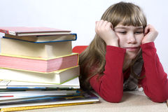 Little cute sad  girl with a pile of book sitting Royalty Free Stock Photography